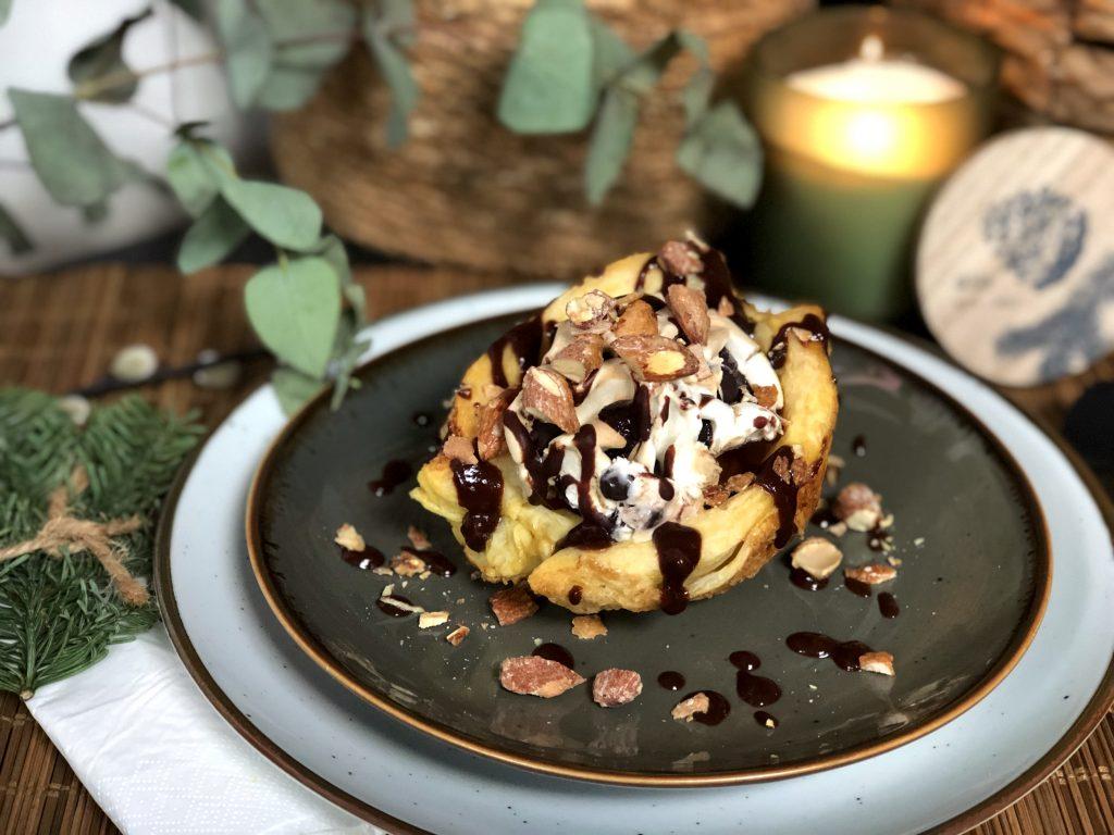 simpel Kerstdessert een gesuikerd bladerdeegbakje met ijs, chocoladesaus, salted caramel en noten