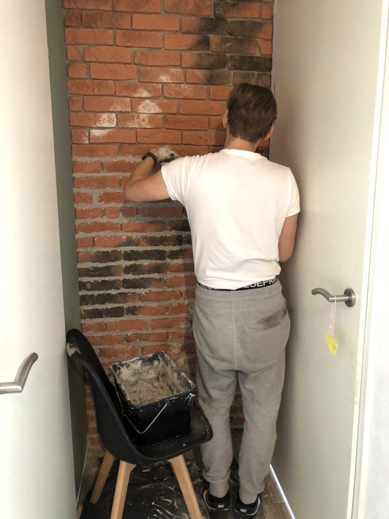 Jan Willem is bezig met het bouwen van een baksteenstrip muur