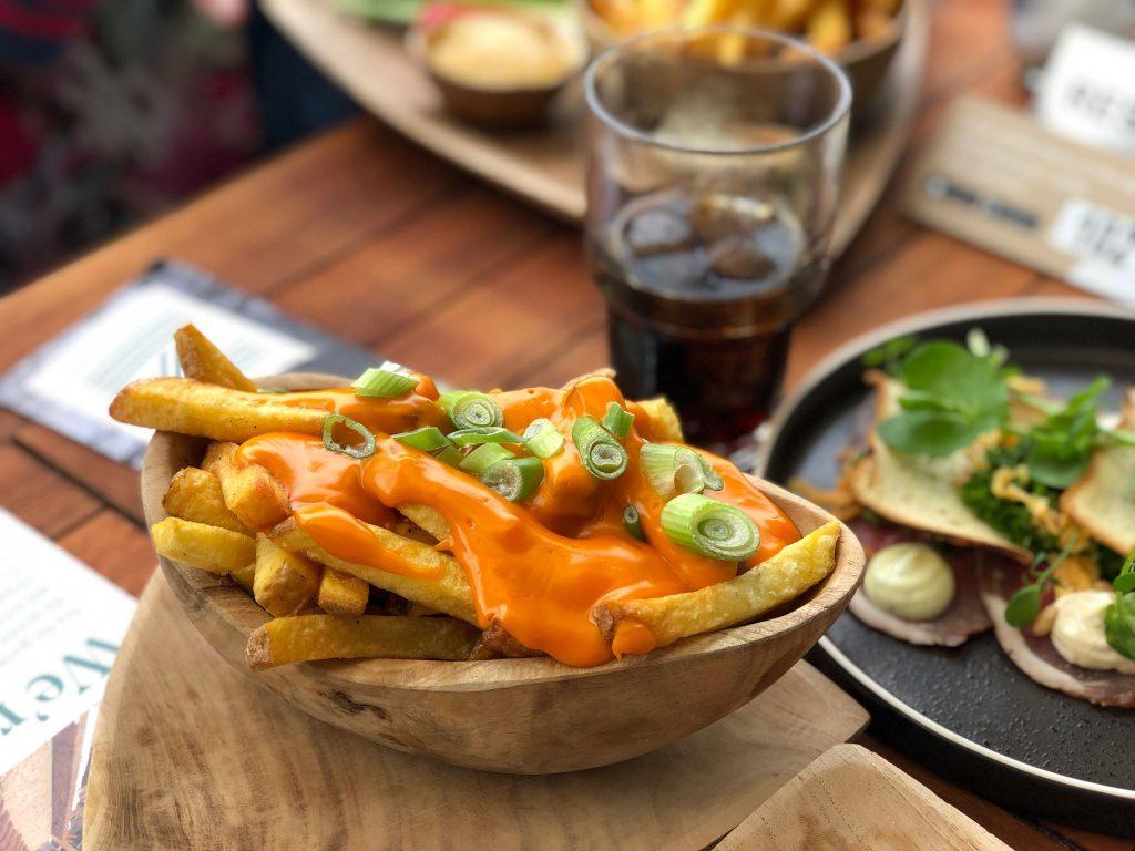 Cheesy friet van Frietboutique met cheddarsaus en bosui bij Strandzuid