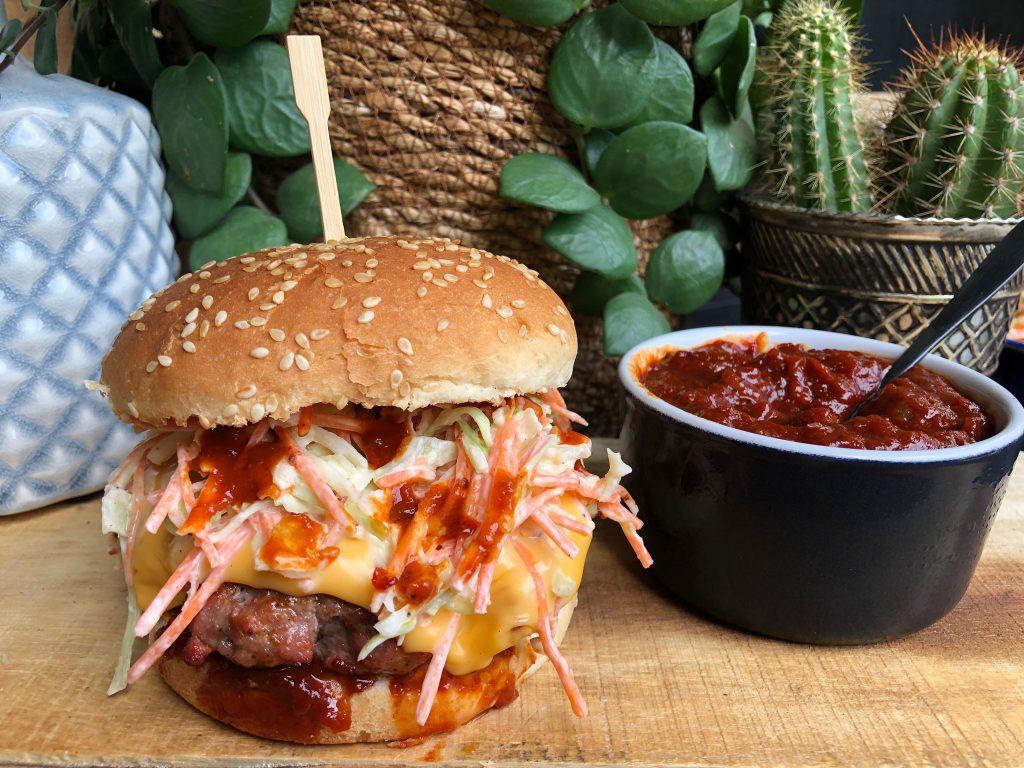 zelfgemaakte bbq saus op een Amerikaanse hamburger met coleslaw