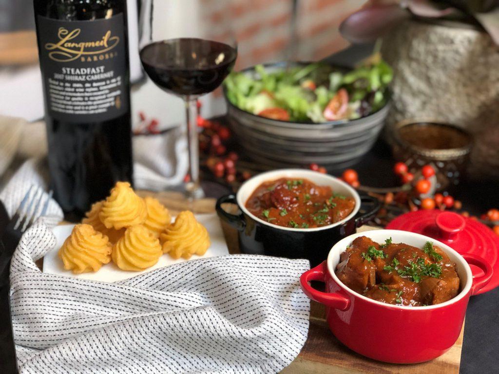 Kip in  rode wijn gestoofd. Serveer met pommes duchesse en een frisse salade.