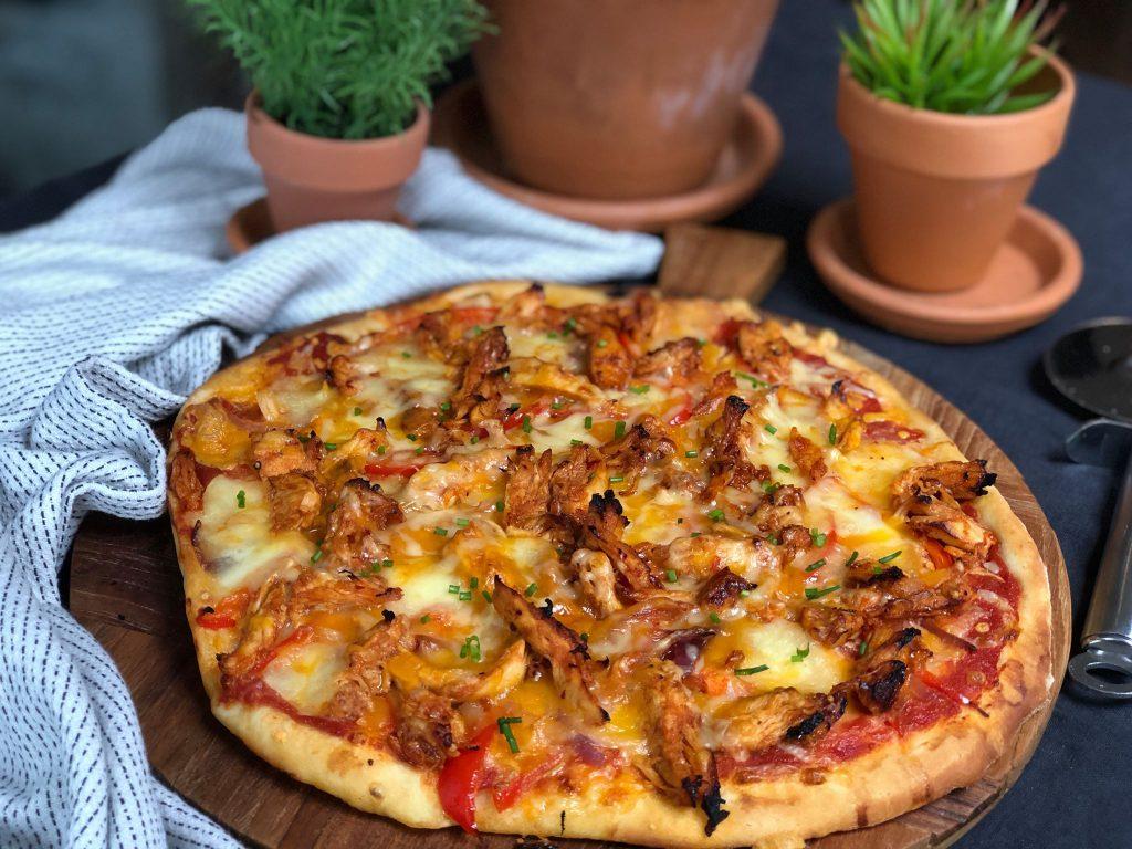 pizza met pikante kip, paprika en rode ui. Lekker met cheddar kaas.