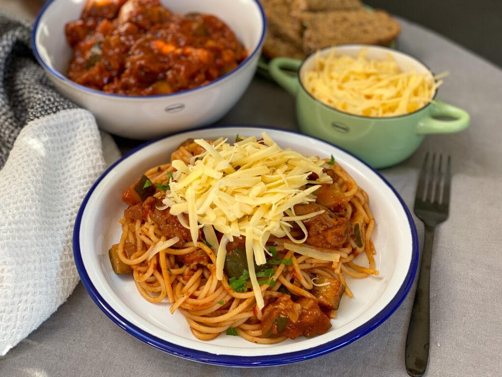 kip stoof in kruidige tomatensaus met pasta en geraspte kaas