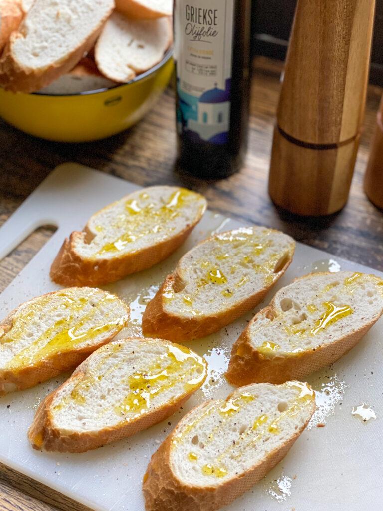 stokbrood besprenkelen met olie om een bruschetta te maken