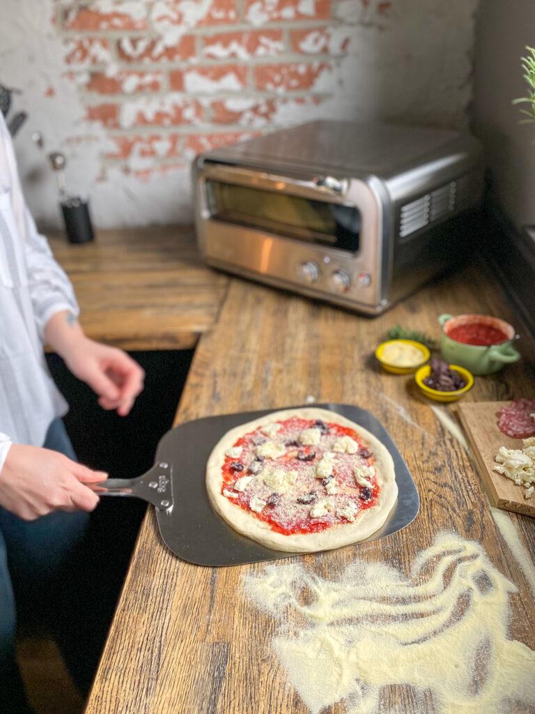 pizza op een pizzaschep scheppen