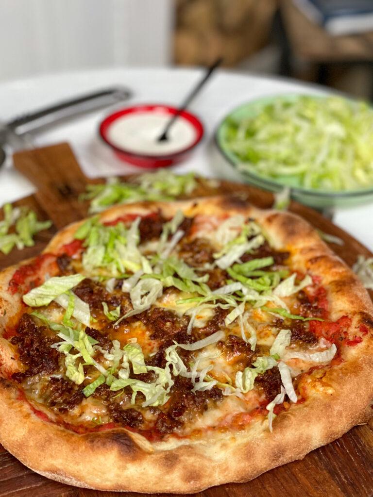 pizza met pittig gehakt en ijsbergsla