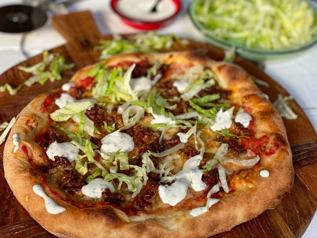 pizza met pittig gehakt, ijsbergsla en frisse saus